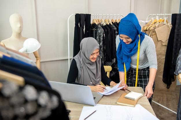 ドレスのスケッチを議論するイスラム教徒の女性ファッションデザイナーチーム
