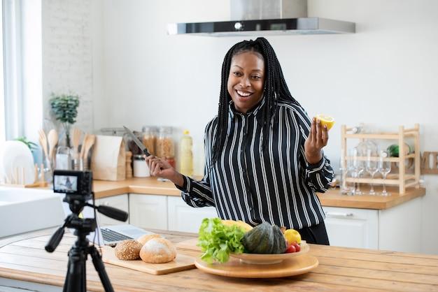 幸せなアフリカ系アメリカ人女性のブロガー放送自宅でライブビデオを調理