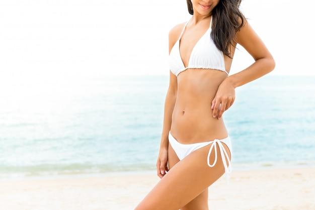 ビーチでポーズをとって白いビキニ水着で美しい形の女性
