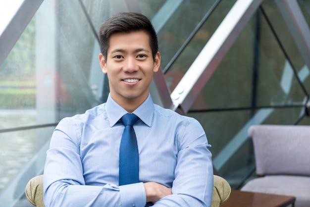 オフィスのラウンジに座っている若い笑顔ハンサムなアジア系のビジネスマン
