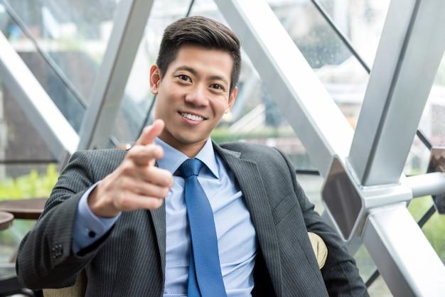 オフィスのラウンジに座っている笑顔のアジア系のビジネスマン