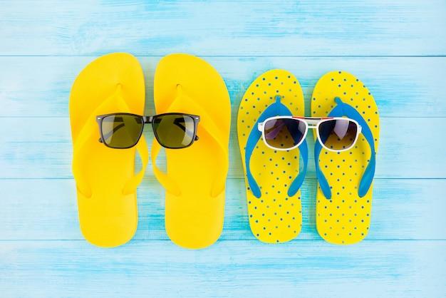 夏のビーチの休日のためのサングラスとカラフルな黄色のフリップフロップ