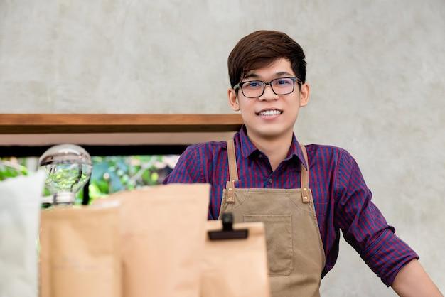 Молодой азиатский предприниматель стоя на прилавке в кофейне