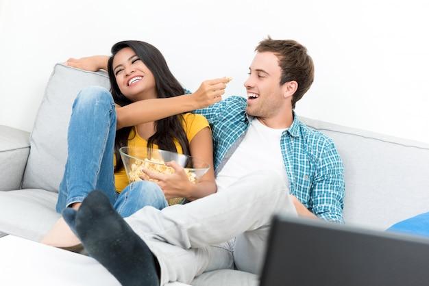 Пара дразнит друг друга пока смотрит телевизор и ест попкорн