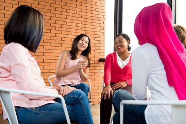 カジュアルな多民族女性の輪の中に座っていると会議で話しています。