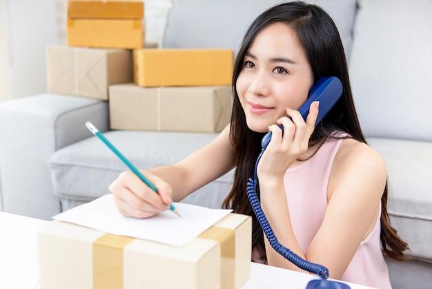 注文を確認するために電話で顧客を呼び出す女性フリーランスの売り手