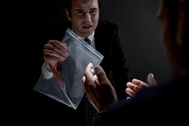 殺人証拠としてナイフを見せている尋問室の警察