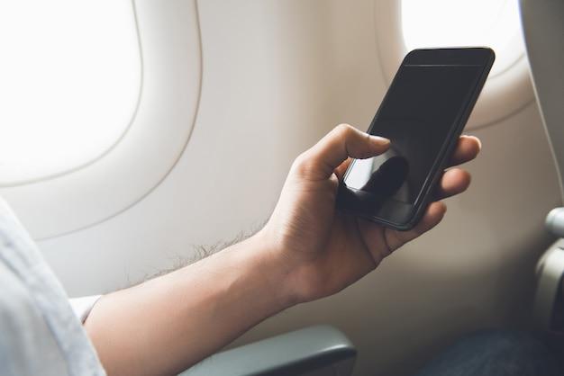 Мужской пассажир отключает мобильный телефон на самолете