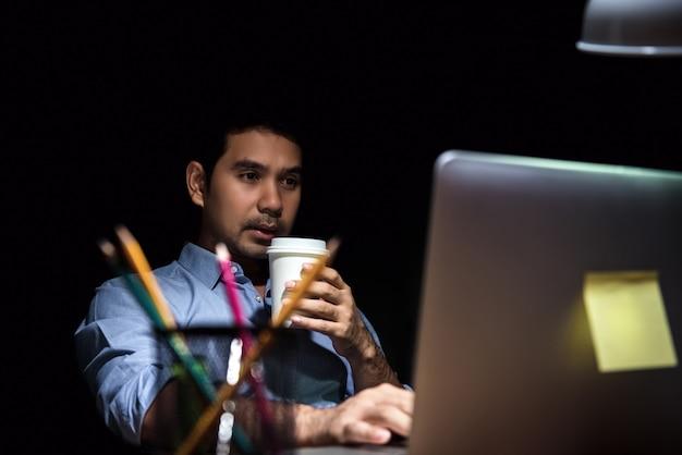 Усталый офисный работник работает перед компьютером в ночное время