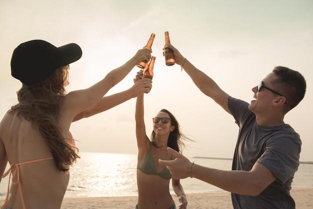 Группа друзей, устраивающих вечеринку, пускающих пивные бутылки на пляже