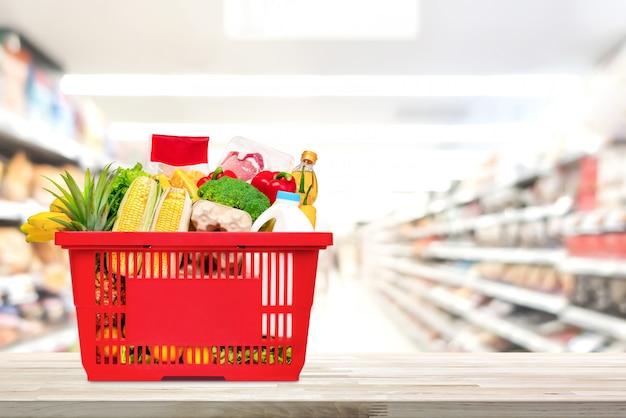 スーパーマーケットのテーブルの上に食べ物や食料品がいっぱい入った買い物かご