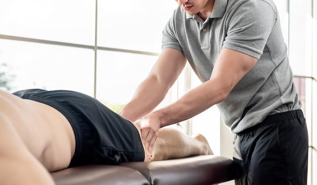 クリニックでベッドの上の運動選手患者に足のマッサージを与える男性セラピスト