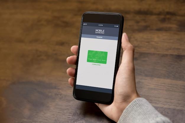 女性がスマートフォンで電子インターネットバンキングアプリケーションを介してオンラインでお金を転送