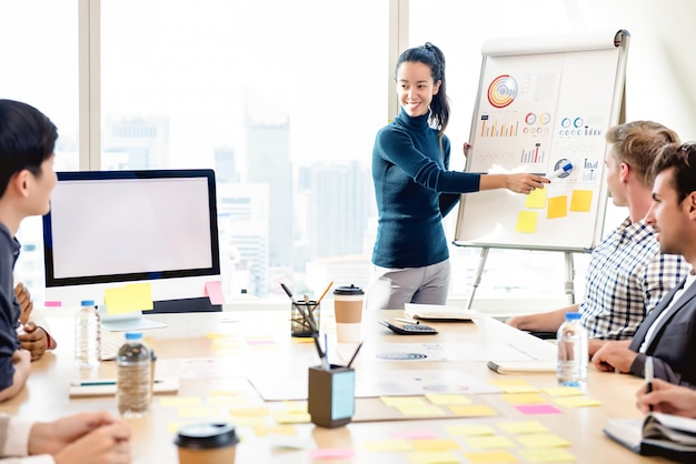 Диаграмма статистики молодой уверенно женщины представляя в встрече офиса