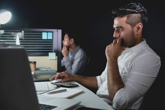 オフィスで働く夜遅くまで残業しているアジアのビジネスマン