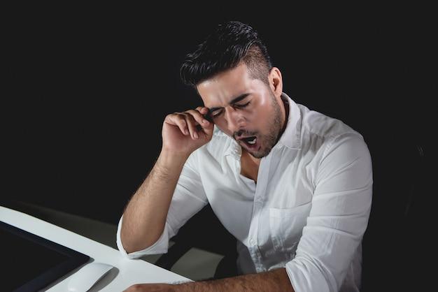 Усталый азиатский бизнесмен чувствует себя сонным и зевая во время работы ночной смены