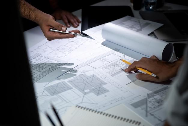 建築家チームのオフィスでの青写真紙を議論します。