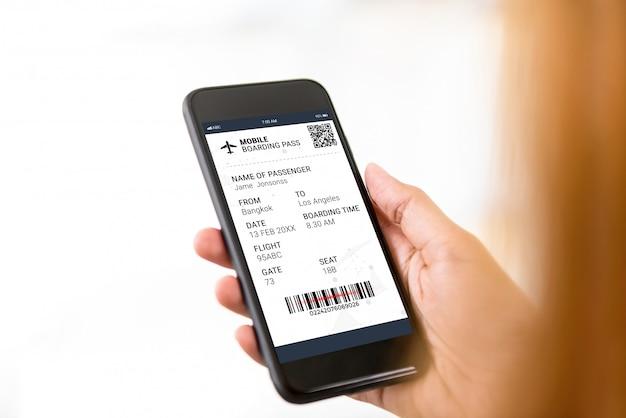 Пассажир смотрит на электронный посадочный талон на экране смартфона