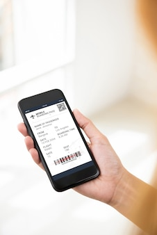 スマートフォンの画面で電子搭乗券を見ている乗客