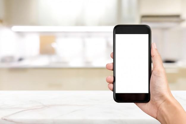 ぼやけキッチンの背景に空の画面を持つ携帯電話