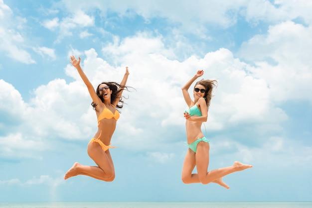 Счастливые друзья женщины в красочных бикини, прыжки на пляже