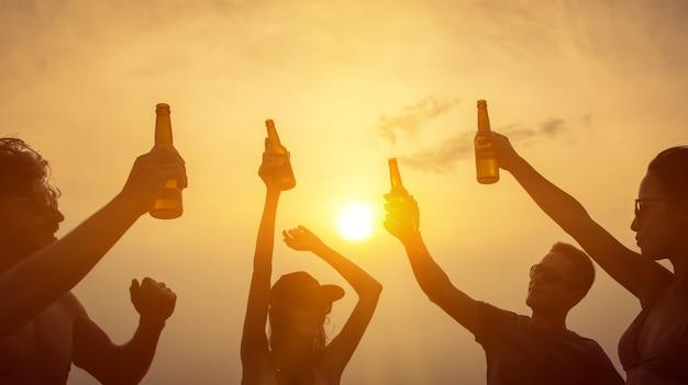 Группа друзей, празднование и пить на пляже в сумерках закат
