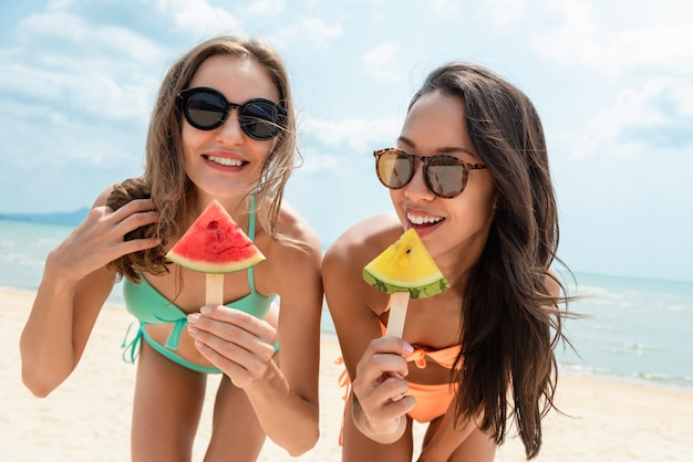 Счастливые красивые друзья женщины на пляже летом
