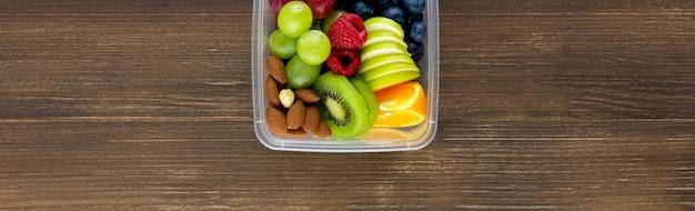 木製のバナーの背景にテイクアウトボックスにアーモンドと健康的な果物