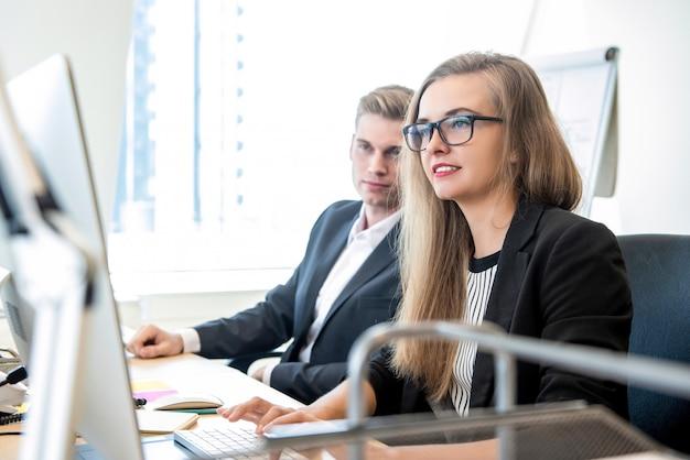 同僚とオフィスでコンピューターに取り組んでいる女性実業家