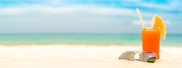 夏の白い砂浜バナー背景でさわやかなフルーツパンチを飲む