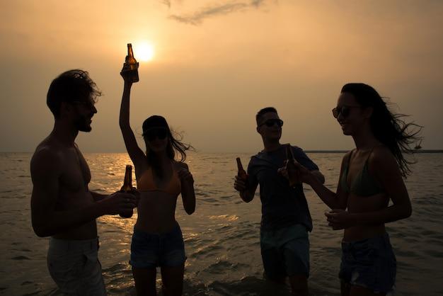 祝うと夕暮れの夕日のビーチで飲んでいる友人のグループ