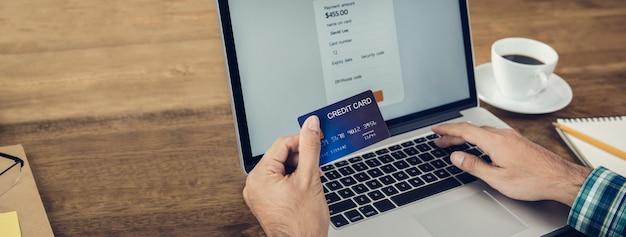 Рука человека, держащего кредитную карту, делая оплату онлайн с ноутбуком