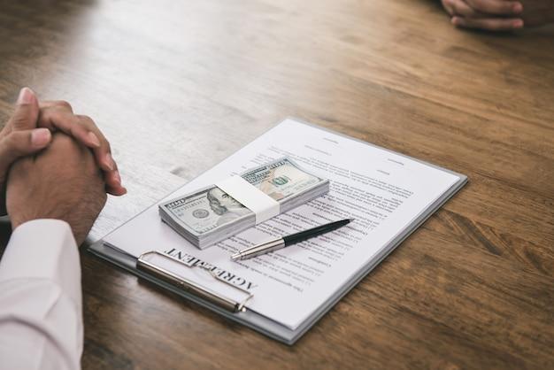 ビジネスマンは彼のパートナーにテーブルの上の契約とお金を提供します。