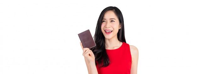 Красивая улыбающаяся азиатская женщина держит паспорт на белом фоне баннера