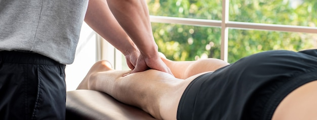 Мужской терапевт дает массаж ног пациенту спортсмена в клинике