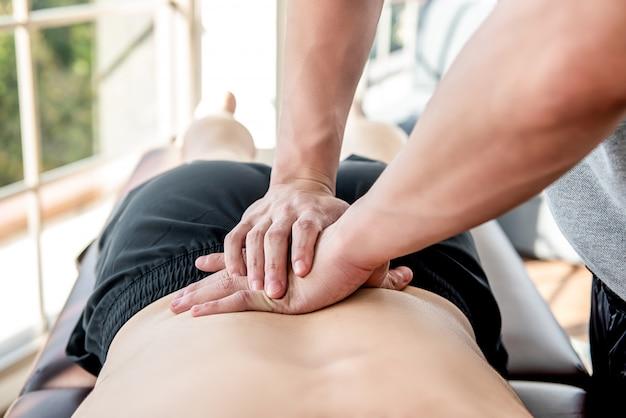 アスリート男性患者に腰スポーツマッサージを与えるセラピスト