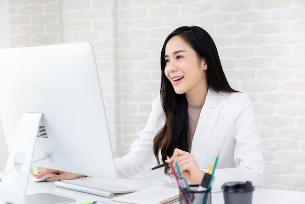 Счастливая красивая азиатская коммерсантка работая на компьютере в офисе