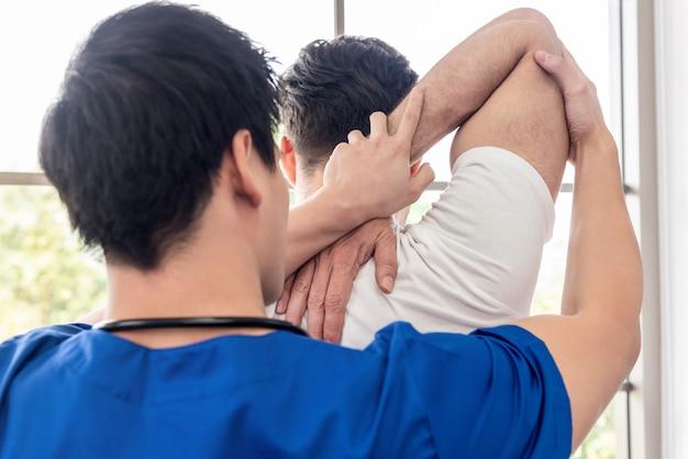 Физиотерапевт растягивает плечо спортсмена мужского пола пациента в клинике