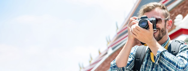 タイのバンコクを旅行中にカメラで写真を撮る男性の観光写真家