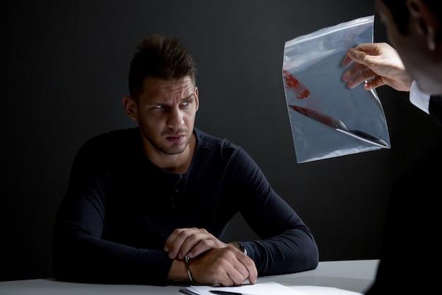 尋問室で殺人証拠としての血でナイフを示す警察