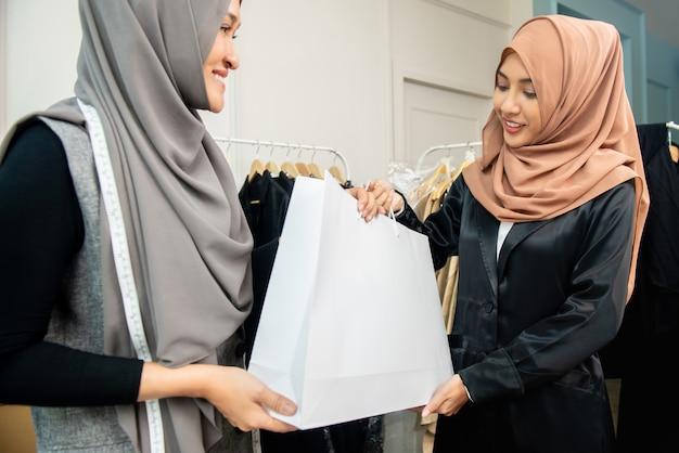 顧客に袋を与えるアジアのイスラム教徒の仕立て屋