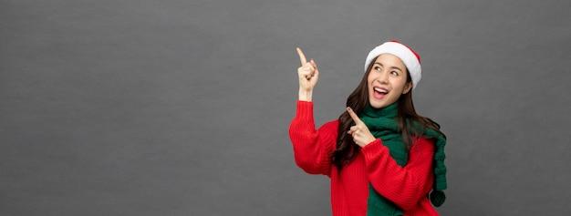 脇の空スペースに手を指しているクリスマスの服装を着て幸せなアジアの女の子