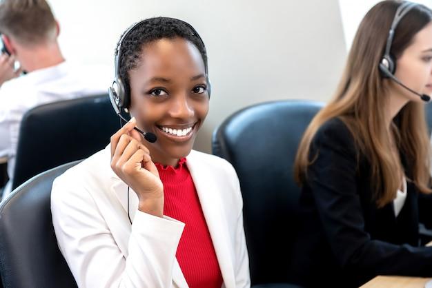多様なチームとのコールセンターで働く笑顔の美しいアフリカ系アメリカ人女性