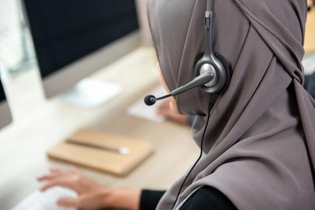 コールセンターのオフィスで働くイスラム教徒の女性カスタマーサービススタッフの背面図