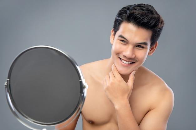 アジアの男性モデルが自信を持って自分を鏡で見ている