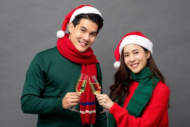 アジアのカップルがクリスマスを祝うシャンパンを飲む