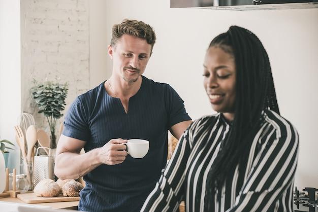台所で異人種間のカップルの結婚生活の朝のルーチン