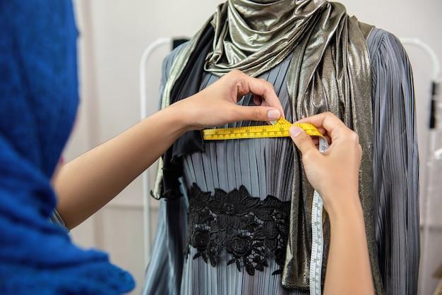 測定テープでドレスのサイズを測定するイスラム教徒のデザイナー