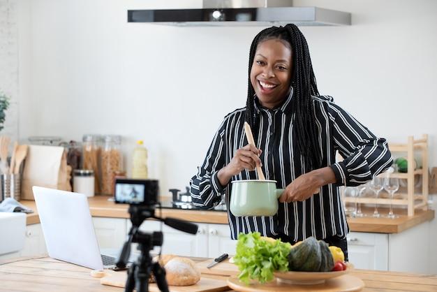アフリカ系アメリカ人の女性が自宅の台所でビデオ録画ビデオを調理