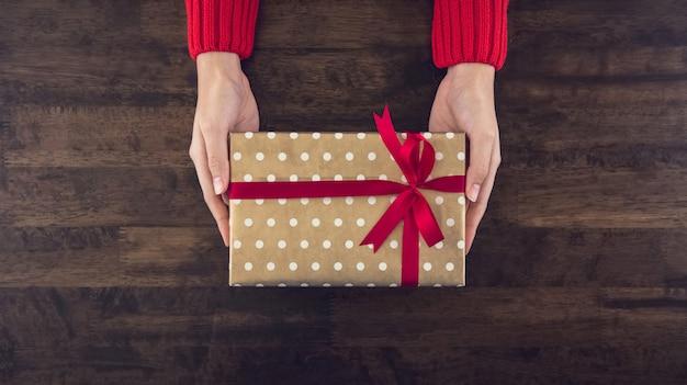 木のテーブルにクリスマスギフトボックストップビューを与える女性の手